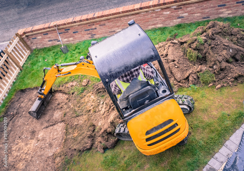 Fotografie, Obraz  mechanical digger seen from above removing turf in front yard, garden for landscaping with artifical grass