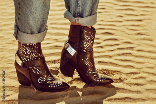 Fotografia, Obraz  Close up photo of black leather cowboy ankle boots with decorative metallic elements