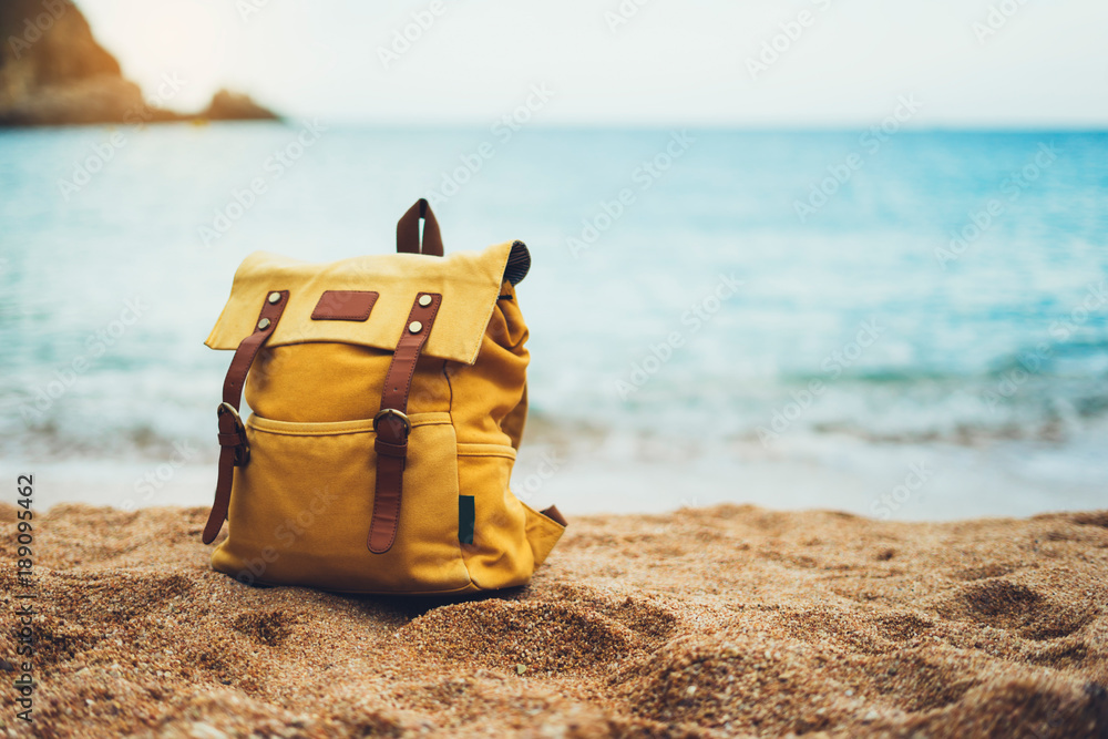 Fototapety, obrazy: hiker tourist yellow backpack closeup on background blue sea enjoying sunset ocean horizon, blurred panoramic seascape sunrise blank, traveler relax holiday concept, sunlight view in trip vacation