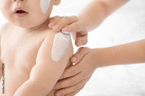Fototapeta Woman applying body cream on her baby against light background