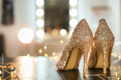 Beautiful high heeled shoes on table with fairy lights