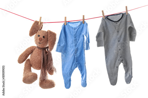 Children's clothes and toy on laundry line against white background #189099013