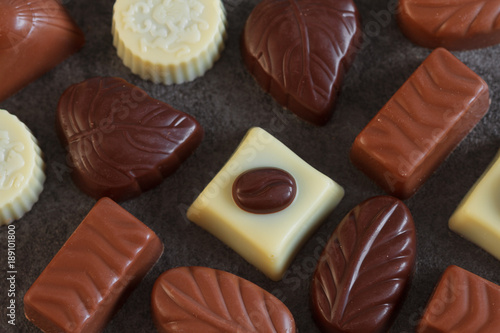 Poster  Assortment of chocolate candies sweets on a dark background