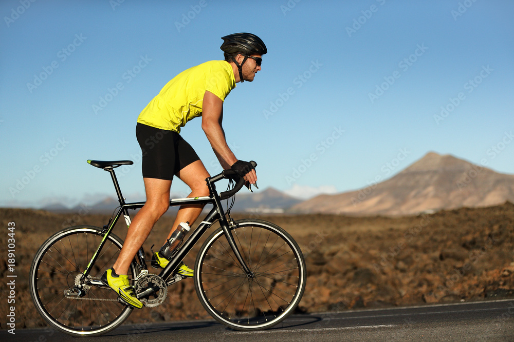 Fototapeta Biking cyclist male athlete going uphill on open road training hard on bicycle outdoors at sunset. Nature landscape.