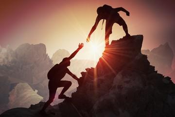 Koncept pomoći i pomoći. Siluete dvoje ljudi koji se penju na planinu i pomažu.