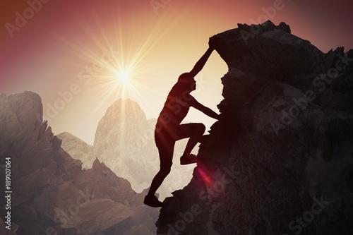 Fototapeta Silhouette of young man climbing on mountain. obraz