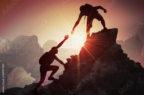 Fototapeta Help and assistance concept. Silhouettes of two people climbing on mountain and helping. obraz