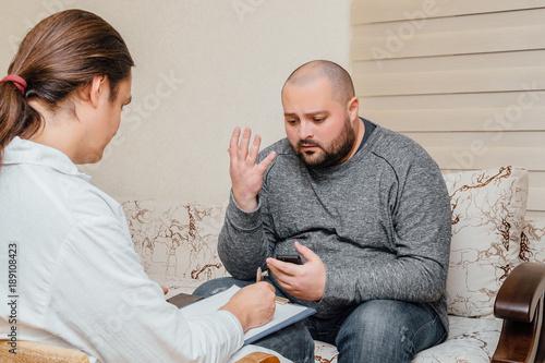 Fotografie, Obraz  Depressive fat man talking with psychologist