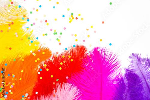 Bright colored feathers for a carnival costume. Color confetti. White background.