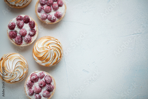Fényképezés  Delicious lemon and raspberry tartlets with meringue on a white vintage plate