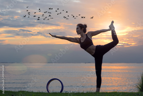 woman yoga wheel posture practice and performance on the sea beach at sunset scenery.