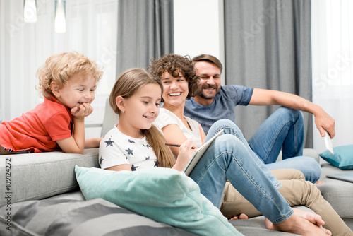 Obraz Joyful family of four gathered together in cozy living room and enjoying each others company, pretty little girl drawing picture with pencil - fototapety do salonu
