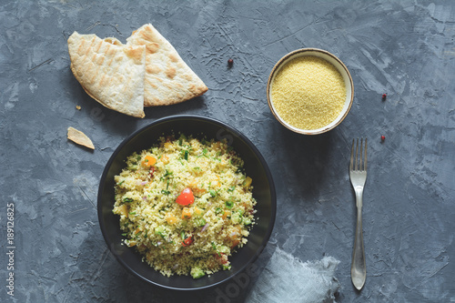 Tabbouleh with cous cous and arabic flatbread on concrete background. Healthy dietetic meal. Table top view