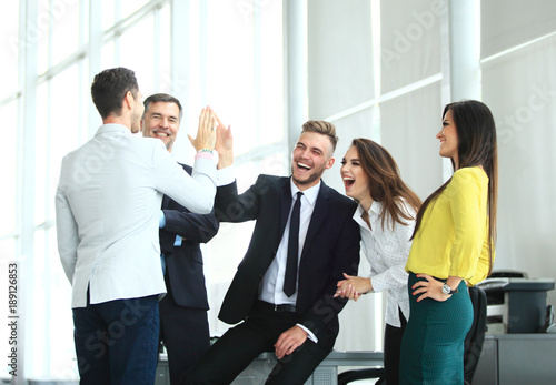 Fototapety, obrazy: Happy successful multiracial business team giving a high fives gesture as they laugh and cheer their success