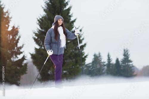 Fotobehang Wintersporten Winter girl in warm activewear skiing in park or forest on weekend
