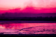 canvas print picture - burning meadow with black smoke on the horizon during the pink-colored sunset