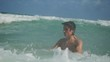 Young handsome man swimming in the sea and splashing wave. slow motion. 1920x1080