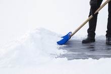 Man Cleaning Snow With Blue Shovel From Ice Surface For Ice Skating. Winter Routine Concept.