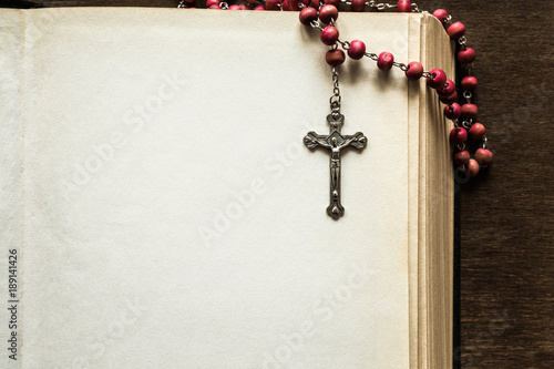 Billede på lærred Opened old thick bible with rosary beads on the brown table in the quiet, dark atmosphere