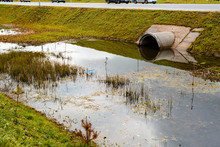 Concrete Culvert Pipe Hole System Draining Sewage Water Near The Puddle. Environmental Disaster