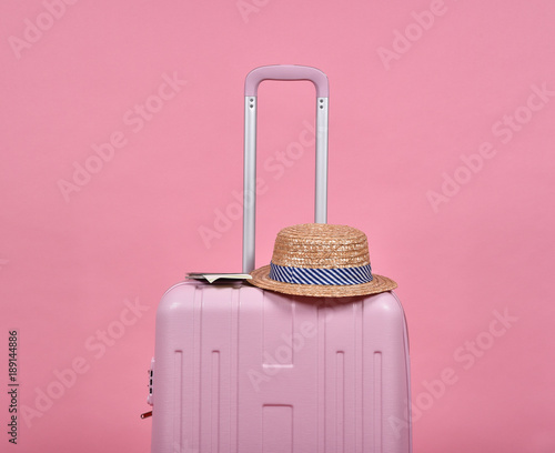 Pink suitcase and passport document over pink background, Journey and travel concept.