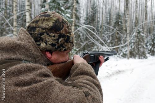 A hunter with a gun. Winter hunting. Huntsman.
