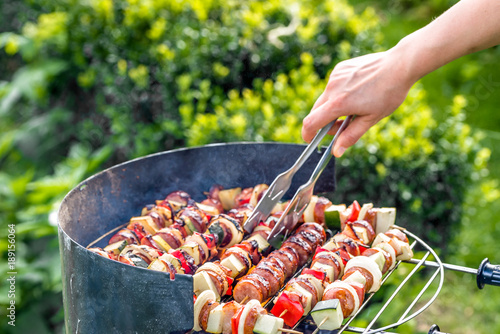 Spoed Foto op Canvas Grill / Barbecue Vegetables and meat kebabs grilled over the coals on barbecue grill, people grilling food outdoors