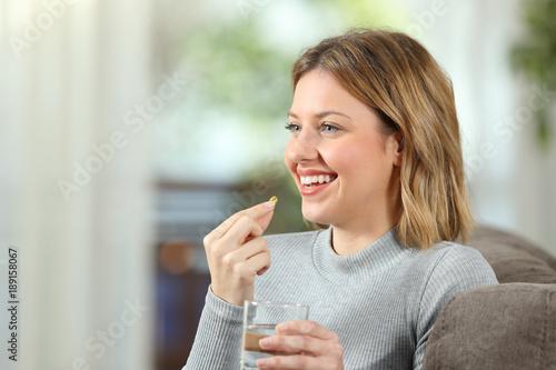 Fototapeta Happy blonde girl taking a vitamin pill at home obraz