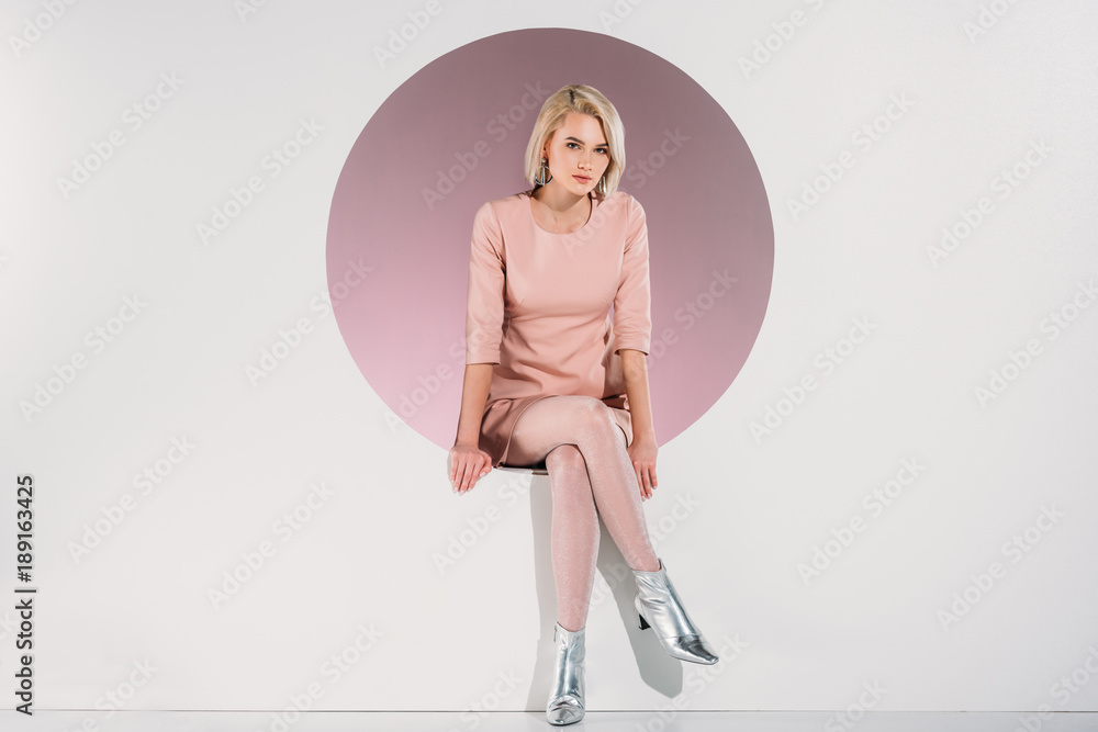Fototapeta beautiful stylish blonde woman in dress and shiny shoes sitting in hole and looking at camera on grey