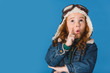 portrait of emotional adorable preteen kid in pilot costume isolated on blue