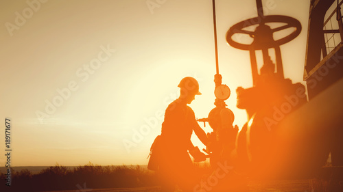 Fotografia  Oil worker is checking the oil pump on the sunset background.