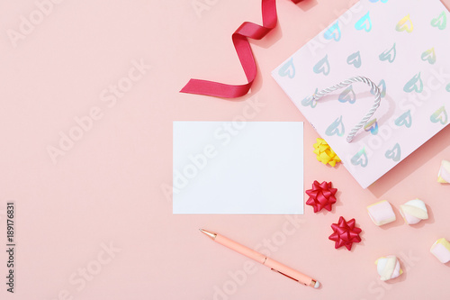 Fotografía  Blank celebration event greeting card and gift bag flat lay on pink background