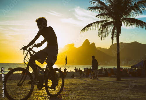 Scenic sunset view of unrecognizable cyclist riding his bike along the Ipanema Beach promenade in Rio de Janeiro, Brazil
