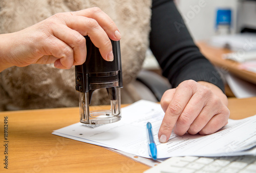female hand with stamp prepare to execute print Fototapet