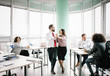 Two managers are imitating dance whil other works at desks. Office concept.