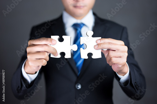 Businessman hands connecting puzzle pieces representing the merging of two companies or joint venture, partnership, Mergers and acquisition concept Wallpaper Mural