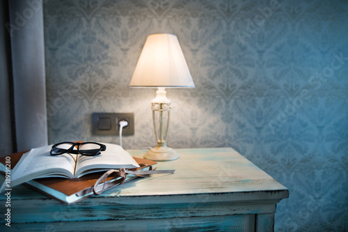 A lamp and a book on a bedside table in a hotel room. Canvas Print