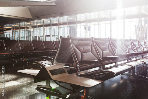 Foto op Aluminium Luchthaven modern airport terminal with black leather seats at sunset.