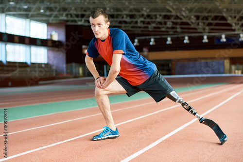 Full length portrait of young amputee sportsman  warming up before running pract Fototapet