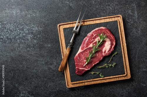 Fotografiet Raw ribeye steak and fork on blackboard