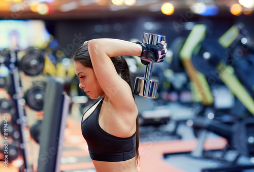 Foto op Canvas Fitness young woman flexing muscles with dumbbell in gym
