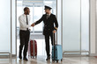 happy handsome pilot handshaking with young businessman at departure area of airport