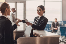 Happy Businesswoman Giving Passport And Ticket To Staff At Airport Check In Counter