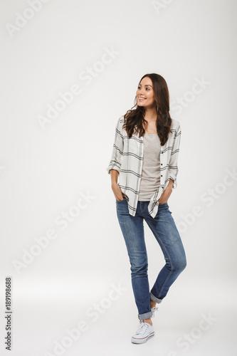 Full length image of Pleased brunette woman in shirt posing Wall mural