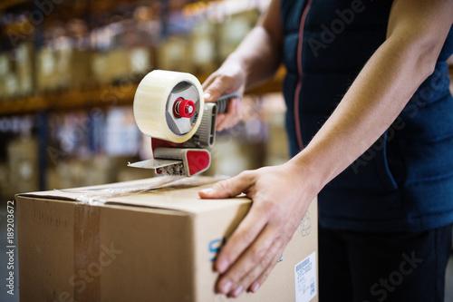 Fotografía  Male warehouse worker sealing cardboard boxes.