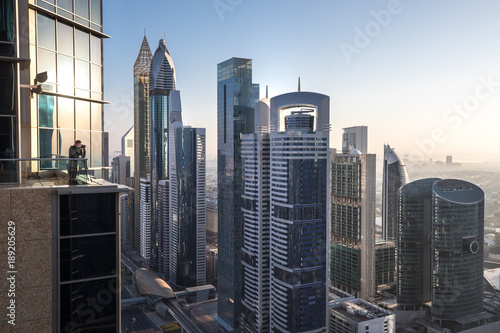 Photo  View of a photographer in Dubai International Financial District at sunrise as viewed from a rooftop viewing point