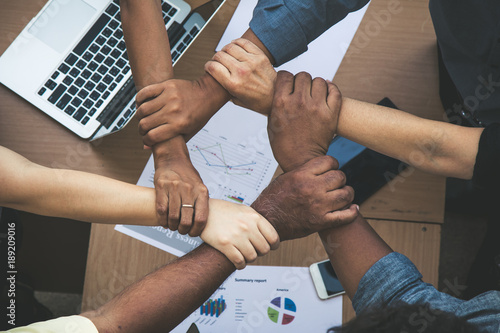Valokuva  Team work concept; close up of joining hands of businessman in unity cross proce
