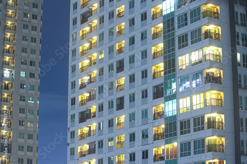 Fotografia Priivacy concept in highrise apartment windows at night lit in cityscape urban highrise buildings