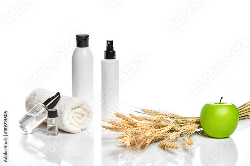 Foto op Plexiglas Spa Spa cosmetics, jar of cream, oil with wheat, white cosmetic bottles with apple and wheat towel, candle, soap isolated on white. Without label.