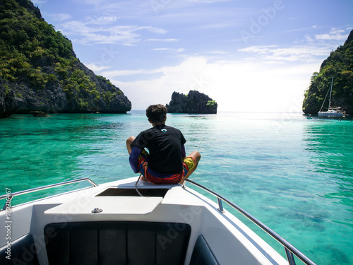 Fotografía Man sit on prow of white sailing boat in Myanmar sea with mountain background